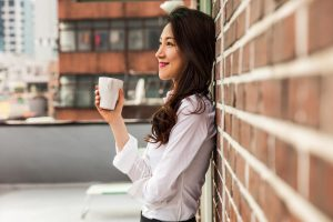 Woman smiling, delighted with her cup of coffee.