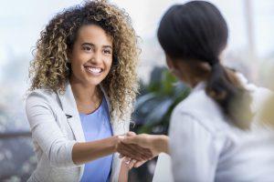 Handshake between two business women.